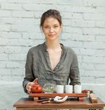 Maître oriental de cérémonie de thé avec le mur de briques blanc sur le fond Thé traditionnel sur la nature avec la femme habillé photographie stock libre de droits