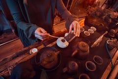 Maître oriental portant une robe grise faisant le thé naturel dans la chambre noire avec un intérieur en bois Tradition, santé images libres de droits