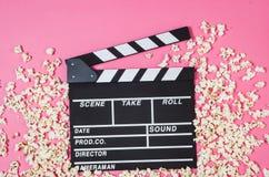 Maïs éclaté, agrafe de film sur la vue supérieure de fond rose, l'espace de copie Image stock