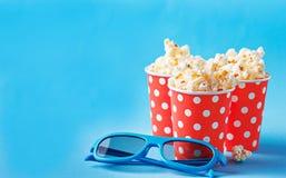 Maïs éclaté avec les verres 3d sur le fond bleu Images libres de droits