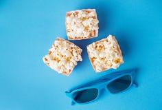 Maïs éclaté avec les verres 3d sur le fond bleu Photographie stock libre de droits