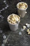Maïs éclaté dans des tasses grises de papier de Noël blanc pour des réunions de vacances d'hiver avec des amis avec le décor de N Image libre de droits