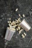 Maïs éclaté dans des tasses grises de papier de Noël blanc pour des réunions de vacances d'hiver avec des amis avec le décor de N Images libres de droits