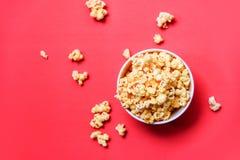 Maïs éclaté dans le seau sur le sel doux de maïs éclaté de beurre de fond rouge photographie stock libre de droits