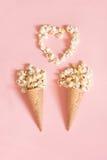 Maïs éclaté dans les cornets de crème glacée sur le fond rose Vue supérieure Image stock