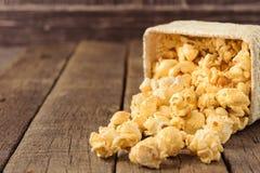Maïs éclaté dans les paniers en osier sur le bois de table Photo stock