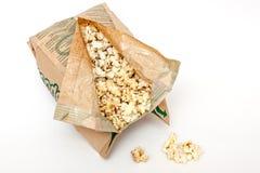Maïs éclaté dans un sac de papier sur le fond blanc Photo libre de droits