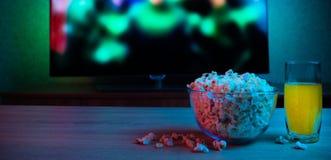 Maïs éclaté dans une glace avec une boisson sur le fond de la TV avec le film dessus Colorez l'éclairage lumineux Reposez-vous, d image libre de droits