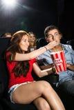 Maïs éclaté de alimentation de femme à l'ami dans le théâtre Photo stock
