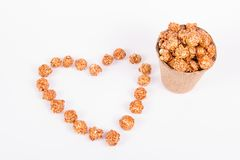 Maïs éclaté de caramel à un seau de papier et à un coeur faits de maïs éclaté Concept romantique Photos stock