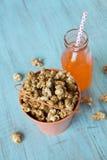 Maïs éclaté de caramel dans le seau avec le soda orange images libres de droits