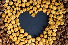 Maïs éclaté de caramel de chocolat avec la forme de coeur Images libres de droits
