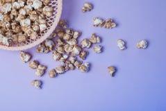 maïs éclaté doux dans un plat en osier sur un fond pourpre, images libres de droits