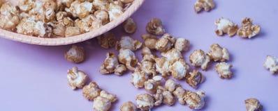 maïs éclaté doux dans un plat en osier sur un fond pourpre, Image libre de droits