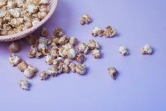 maïs éclaté doux dans un plat en osier sur un fond pourpre, photo stock