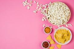Maïs éclaté et pommes chips dans la cuvette sur la vue supérieure de fond rose Images libres de droits