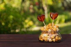 Maïs éclaté et sucreries sous forme de coeur Vase avec le maïs éclaté et la lucette Concept romantique Photographie stock
