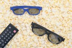 maïs éclaté frit découvert, plan rapproché, comme fond avec une paire des verres 3D et d'une TV à télécommande images stock