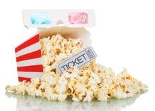 Maïs éclaté lâche dans la boîte carrée rayée, un billet au cinéma et verres 3D d'isolement sur le blanc Photo stock