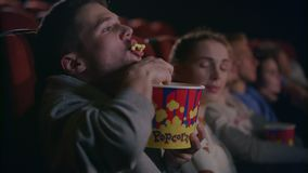 Maïs éclaté mangeur d'hommes grossier au cinéma Façons grossières au hall de film banque de vidéos