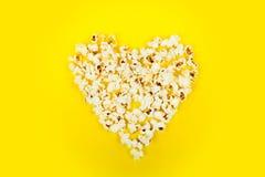 Maïs éclaté pelucheux blanc en forme de coeur sur le fond jaune Image libre de droits