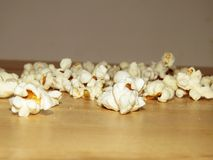 Maïs éclaté salé renversé sur la table photos stock