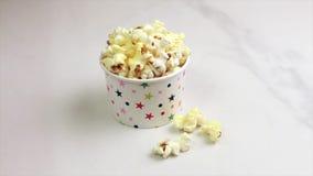 Maïs éclaté salé savoureux dans la tasse de papier sur le fond de marbre clair banque de vidéos