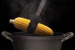 Maïs chaud de pot avec la vapeur sur le fond noir Image libre de droits
