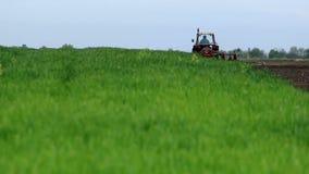 Maïs d'encemencement de ressort avec un tracteur et un planteur banque de vidéos