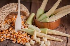 Maïs de graine et maïs de bébé sur le fond en bois de table Photo stock