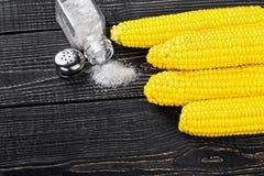 Maïs et sel sur une table en bois Photographie stock libre de droits