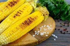 Maïs grillé savoureux frais avec du beurre, le sel de mer et le cilantro sur une table en bois Image stock