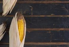 Maïs jaune mûr sur une vieille table en bois foncée Photographie stock