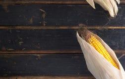 Maïs jaune mûr sur une vieille table en bois foncée Photographie stock libre de droits