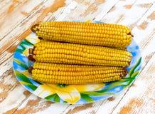Maïskolven van gekookt graan in een ceramische schotel op witte houten lijst Royalty-vrije Stock Afbeeldingen