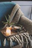 Mañana acogedora del invierno en casa Cacao o café caliente con la vela en silla nórdica azul del estilo Fotografía de archivo
