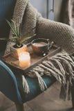 Mañana acogedora del invierno en casa Cacao o café caliente con la vela en silla nórdica azul del estilo Foto de archivo
