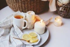 Mañana acogedora del invierno en casa Té caliente con el limón, los suéteres hechos punto y los detalles interiores metálicos mod Imagen de archivo libre de regalías