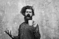 Mañana Coffe hombre barbudo cantante que tira del pelo elegante de la franja con la taza azul fotografía de archivo