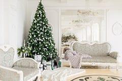 Mañana de la Navidad apartamentos clásicos con una chimenea blanca, árbol adornado, sofá brillante, ventanas grandes Fotografía de archivo libre de regalías