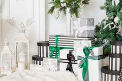 Mañana de la Navidad apartamentos clásicos con una chimenea blanca, árbol adornado, sofá brillante, ventanas grandes Foto de archivo libre de regalías