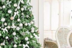 Mañana de la Navidad apartamentos clásicos con una chimenea blanca, árbol adornado, sofá brillante, ventanas grandes Fotografía de archivo