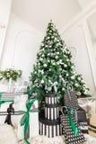 Mañana de la Navidad apartamentos clásicos con una chimenea blanca, árbol adornado, sofá brillante, ventanas grandes Fotos de archivo