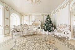Mañana de la Navidad apartamentos clásicos con una chimenea blanca, árbol adornado, sofá brillante, ventanas grandes Imagen de archivo