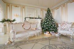 Mañana de la Navidad apartamentos clásicos con una chimenea blanca, árbol adornado, sofá brillante, ventanas grandes Imagenes de archivo