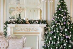 Mañana de la Navidad apartamentos clásicos con una chimenea blanca, árbol adornado, sofá brillante, ventanas grandes Foto de archivo