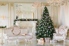 Mañana de la Navidad apartamentos clásicos con una chimenea blanca, árbol adornado, sofá brillante, ventanas grandes Fotos de archivo libres de regalías