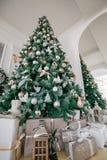 Mañana de la Navidad apartamentos de lujo clásicos con una chimenea blanca, árbol adornado, sofá brillante, ventanas grandes Fotografía de archivo libre de regalías