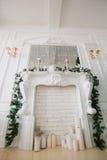 Mañana de la Navidad apartamentos de lujo clásicos con una chimenea blanca, árbol adornado, sofá brillante, ventanas grandes Imagenes de archivo