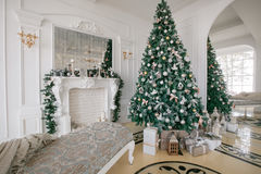 Mañana de la Navidad apartamentos de lujo clásicos con una chimenea blanca, árbol adornado, sofá brillante, ventanas grandes Fotos de archivo